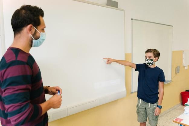Schülerjunge mit maske, die während seines unterrichts mit seinem lehrer auf die tafel zeigt. zurück zur schule während der koviden pandemie, die soziale distanz bewahrt.