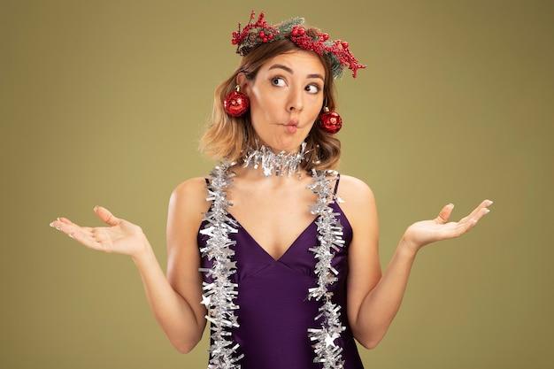 Schürzende lippen junges schönes mädchen, das lila kleid und kranz mit girlande am hals trägt, die weihnachtsbaumkugeln auf den ohren hält und die hände einzeln auf olivgrünem hintergrund ausbreitet Kostenlose Fotos