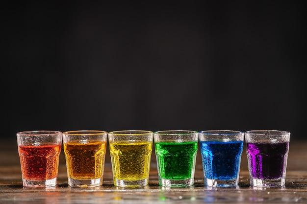 Schüsse mit mehrfarbigem alkohol, in einer reihe stehend