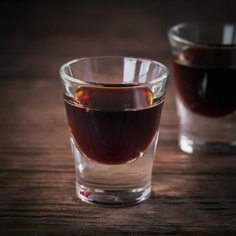 Schüsse von alkoholischem getränk auf dunklem holzhintergrund. kräuterbitterlikör mit verschiedenen natürlichen zutaten. nahaufnahme