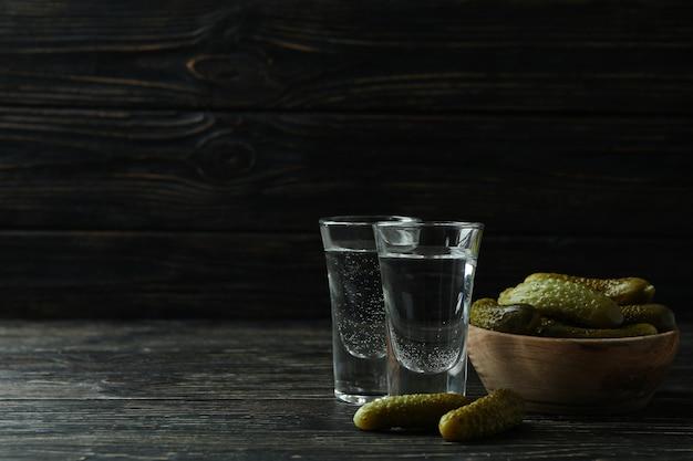 Schüsse von wodka und gurken auf hölzernem hintergrund