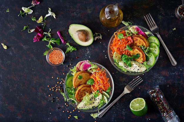 Schüssel-abendessentabelle des strengen vegetariers buddha. gesundes essen. gesunde vegane lunch bowl. krapfen mit linsen und rettich, avocado, karottensalat. flach liegen.