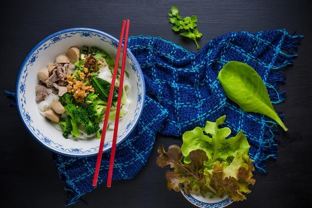 Schüssel asiatische nudeln mit gemüse und pak auf holztisch.