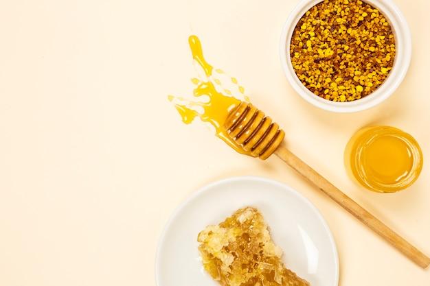 Schüssel blütenstaub mit bienenwabe und honigglas