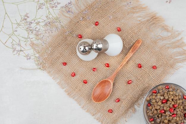 Schüssel bohnen mit granatapfelkernen und salz auf sackleinen.