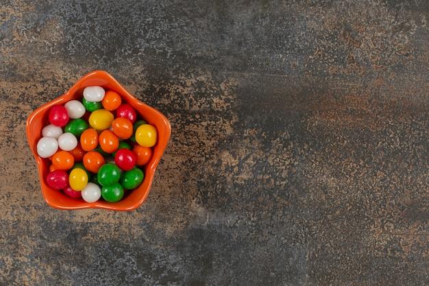 Schüssel bunte bonbons auf marmor.