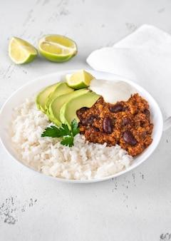 Schüssel chili con carne mit reis, avocado und sauerrahm