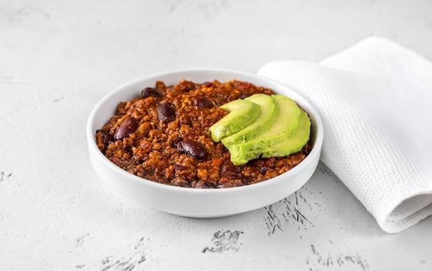 Schüssel chili mit fleisch mit avocado-scheiben