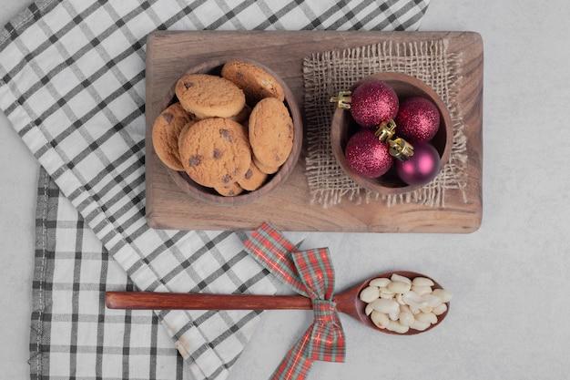 Schüssel chipkekse und weihnachtskugeln auf weißem tisch. hochwertiges foto
