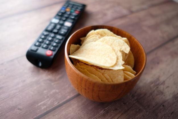 Schüssel chips und tv-fernbedienung auf hölzernem hintergrund.