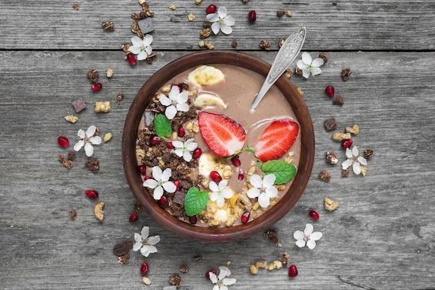 Schüssel choclate und bananen-smoothie mit schokoladenmüsli, erdbeer- und granatapfelkernen mit einem löffel