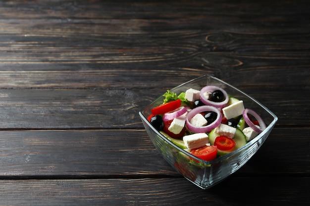 Schüssel des griechischen salats auf hölzernem hintergrund