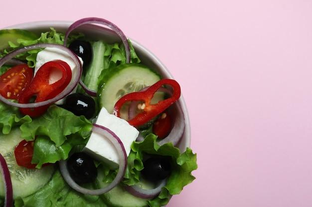 Schüssel des griechischen salats auf rosa hintergrund, platz für text