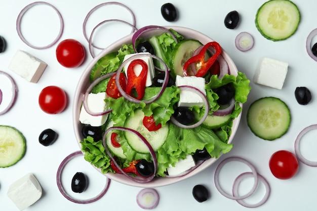 Schüssel des griechischen salats und der bestandteile auf weißem hintergrund, draufsicht