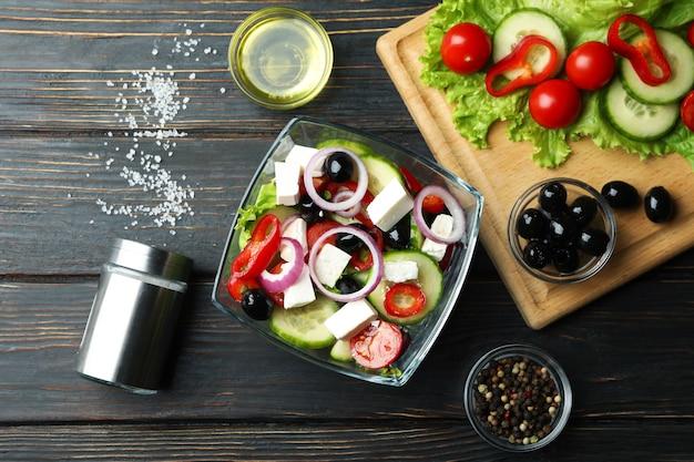 Schüssel des griechischen salats und der zutaten auf hölzernem hintergrund
