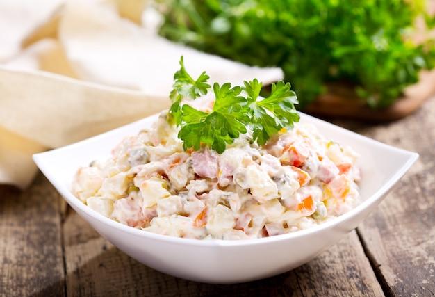Schüssel des traditionellen russischen salats auf holztisch