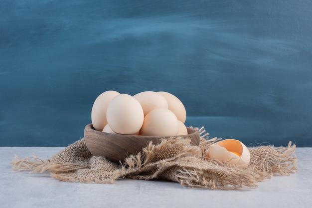 Schüssel eier neben eigelb in einer schale auf einem stück stoff auf marmortisch.