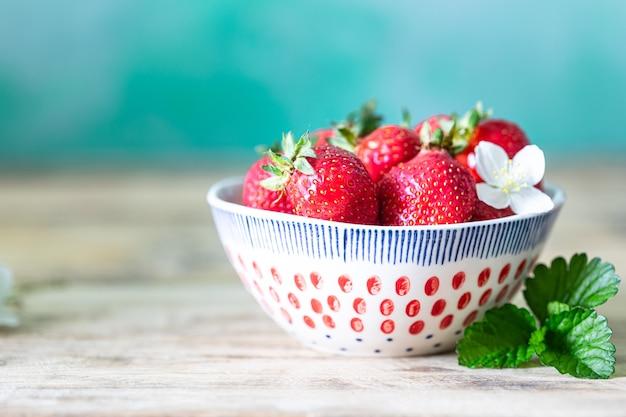 Schüssel erdbeeren auf einem holz.