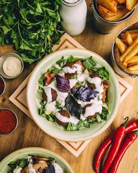 Schüssel fleischklöschensalat geschmückt mit jogurtsoße