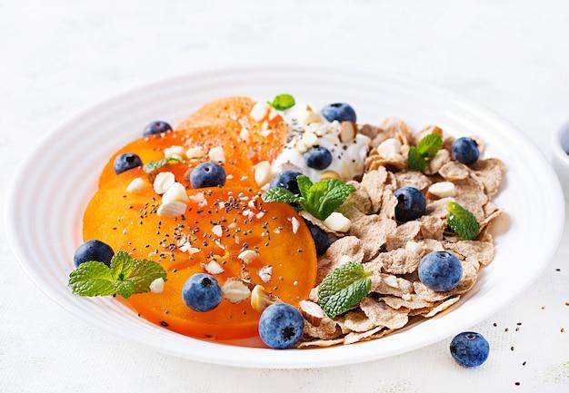 Schüssel flocken mit joghurt, blaubeeren und kaki auf weißem holztisch. fitness essen.