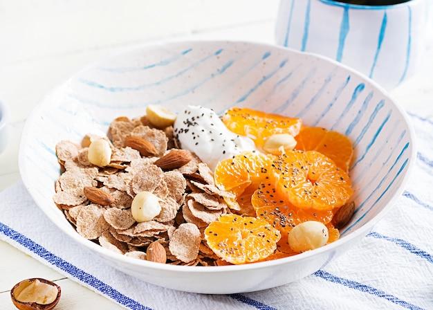 Schüssel flocken mit joghurt und mandarine auf weißem holztisch. fitness essen.