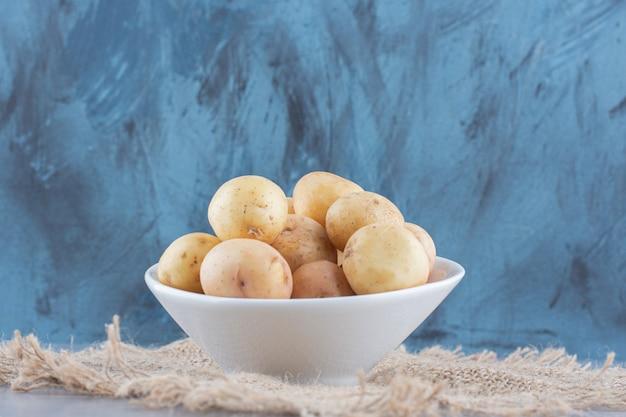 Schüssel frische bio-kartoffel auf sack.