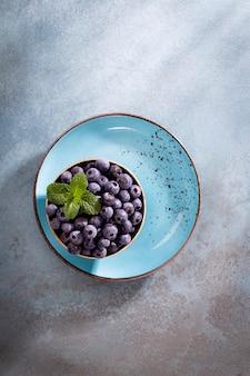 Schüssel frische blaubeeren auf rustikalem holzbrett. bio-lebensmittel blaubeeren und minzblatt für einen gesunden lebensstil.