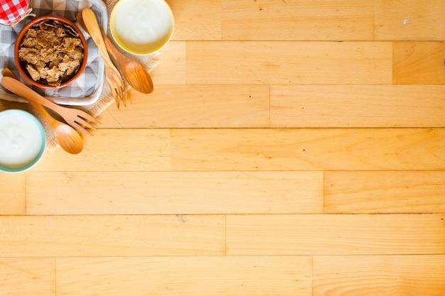 Schüssel frische frucht mit bananenapfel-erdbeeraprikosenblaubeerpflaumen-vollkorn gabelt draufsicht