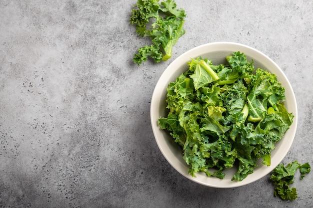 Schüssel frischer grüner gehackter grünkohl auf grauem rustikalem steinhintergrund, draufsicht, nahaufnahme, kopienraum. zutat für die herstellung eines gesunden salats. sauberes essen, entgiftung oder diätkonzept mit platz für text