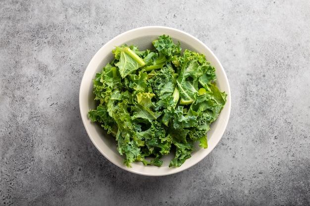 Schüssel frischer grüner gehackter grünkohl auf grauem rustikalem steinhintergrund, draufsicht, nahaufnahme. zutat für die herstellung eines gesunden salats. clean eating, detox oder diätkonzept