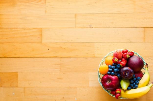 Schüssel frisches obst mit banane, apfel, erdbeeren, aprikosen, blaubeeren, pflaumen, vollkornprodukten, gabeln, draufsicht