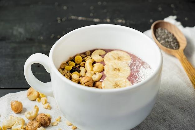 Schüssel frucht smoothie, nüsse und banane. acai-schüssel mit getreide, acajoubäumen und haselnüssen auf rustikaler tabelle der weinlese
