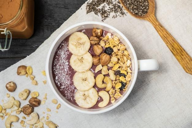 Schüssel frucht smoothie, nüsse und banane, draufsicht. flache lage einer acai-schüssel mit getreide, acajoubäumen und haselnüssen auf rustikaler tabelle der weinlese
