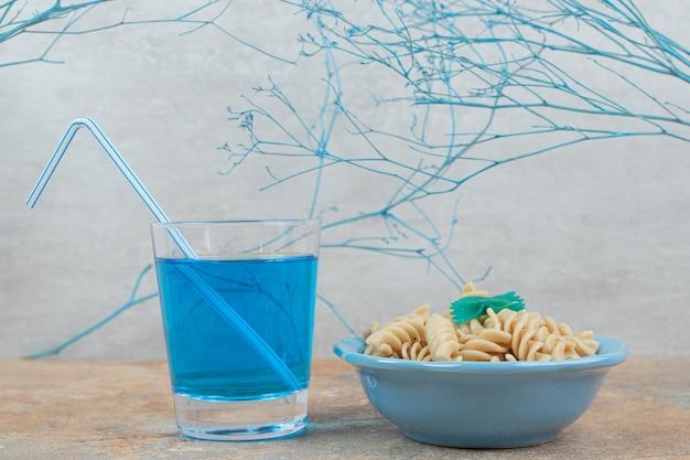 Schüssel fusilli-nudeln und glas blauen cocktail auf marmorhintergrund