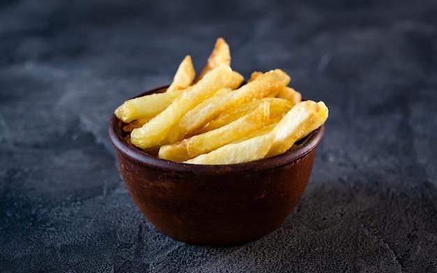 Schüssel gefüllt mit knusprigen pommes frites auf dem tisch