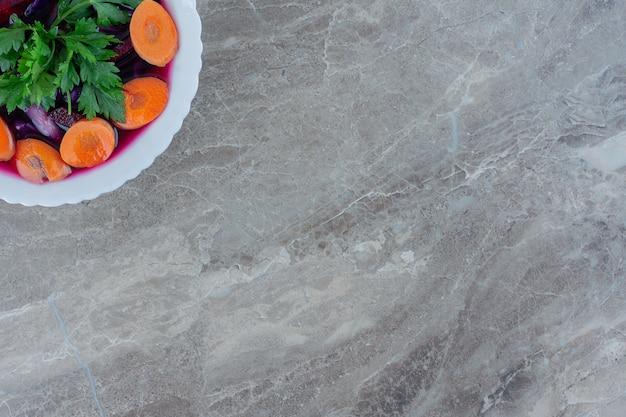 Schüssel gehackte rote beete, garniert mit karottenscheiben und petersilienblättern auf marmor.