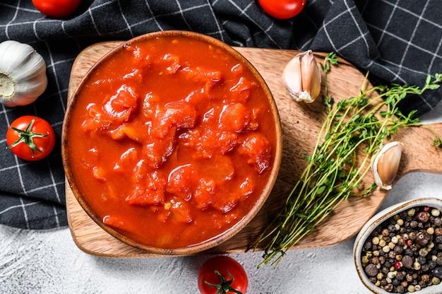 Schüssel gehackte tomaten lokalisiert auf rustikaler weißer oberfläche. weißer hintergrund. draufsicht