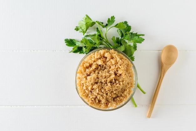 Schüssel gekochte quinoa mit petersilie auf einem weißen tisch verziert. der blick von oben. flach liegen.