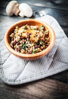 Schüssel gekochter buchweizen mit gebratenem champignon, spinat und roten bohnen
