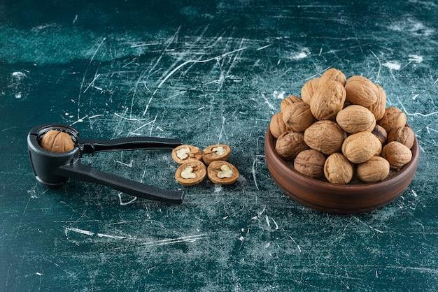 Schüssel geschälte walnüsse mit nussknackwerkzeug auf marmortisch.