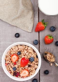 Schüssel gesundes getreidemüsli mit erdbeeren und blaubeeren und glas milch auf hölzernem brett