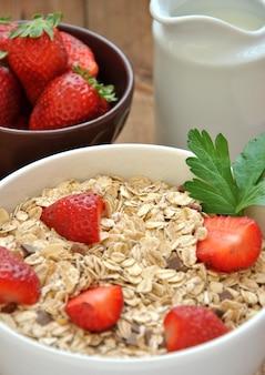 Schüssel getreide mit milch und erdbeeren auf holztisch