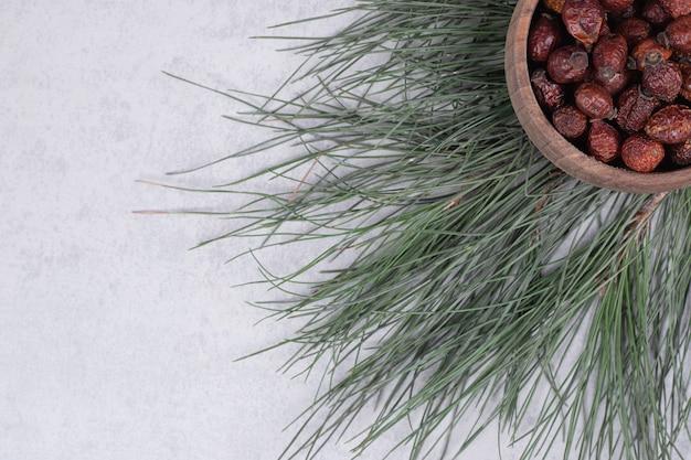 Schüssel getrocknete preiselbeeren und tannenzweig auf marmortisch. hochwertiges foto