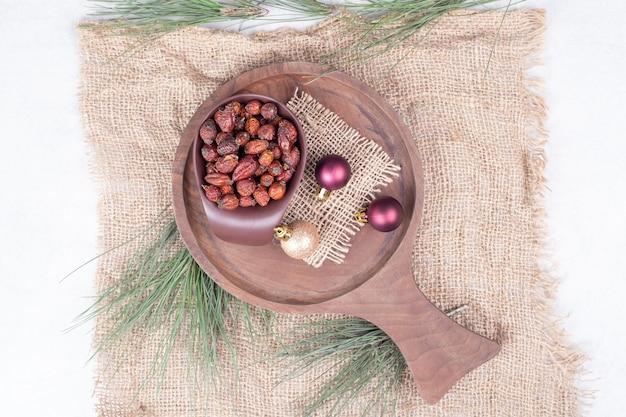 Schüssel getrocknete preiselbeeren und weihnachtskugeln auf holzbrett. hochwertiges foto