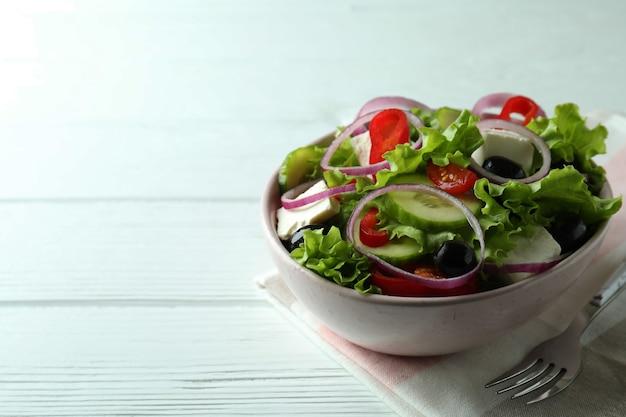 Schüssel griechischen salats auf weißem holz