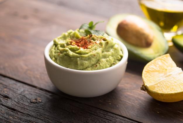 Schüssel grüner hummus, köstliche kichererbsencreme und avocado auf einer holzoberfläche.