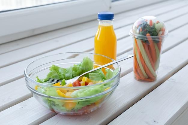 Schüssel grüner salat, rohes gemüse und flasche orangensaft. gewichtsverlust, ernährung und richtig