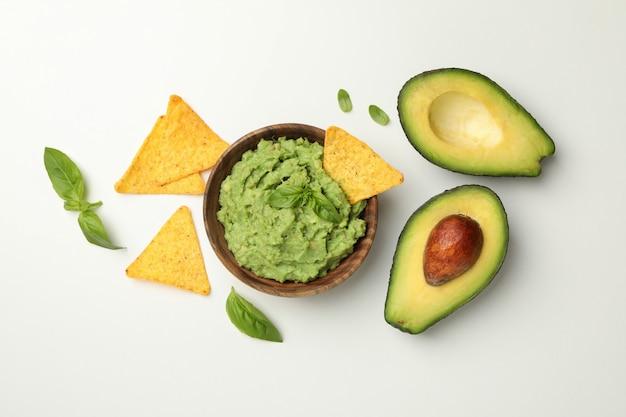 Schüssel guacamole, avocado, chips und basilikum auf weißem hintergrund, draufsicht
