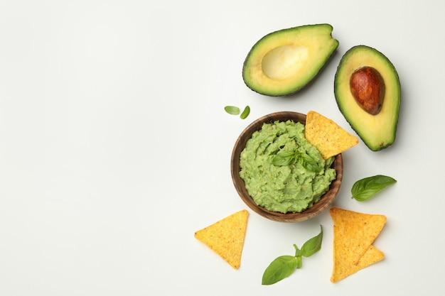 Schüssel guacamole, avocado, chips und basilikum auf weißem hintergrund, platz für text