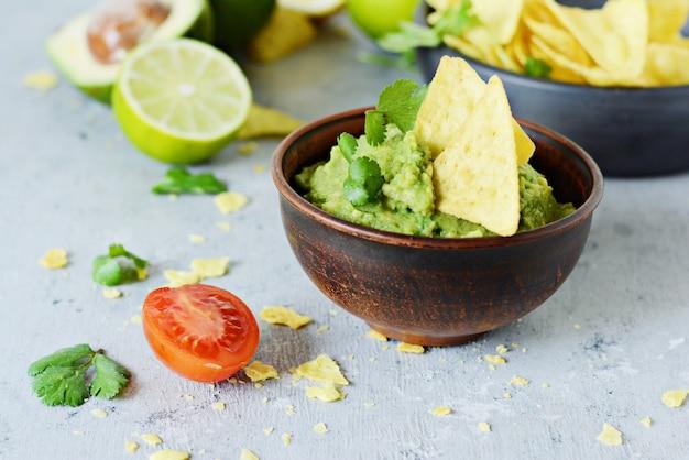 Schüssel guacamole dip mit mais nachos (chips) und zutaten auf blauem hintergrund, selektiver fokus. mexikanisches nationalgericht.